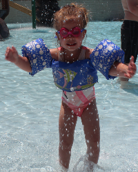 Young Girl in Floating and Goggles Playing in the Water