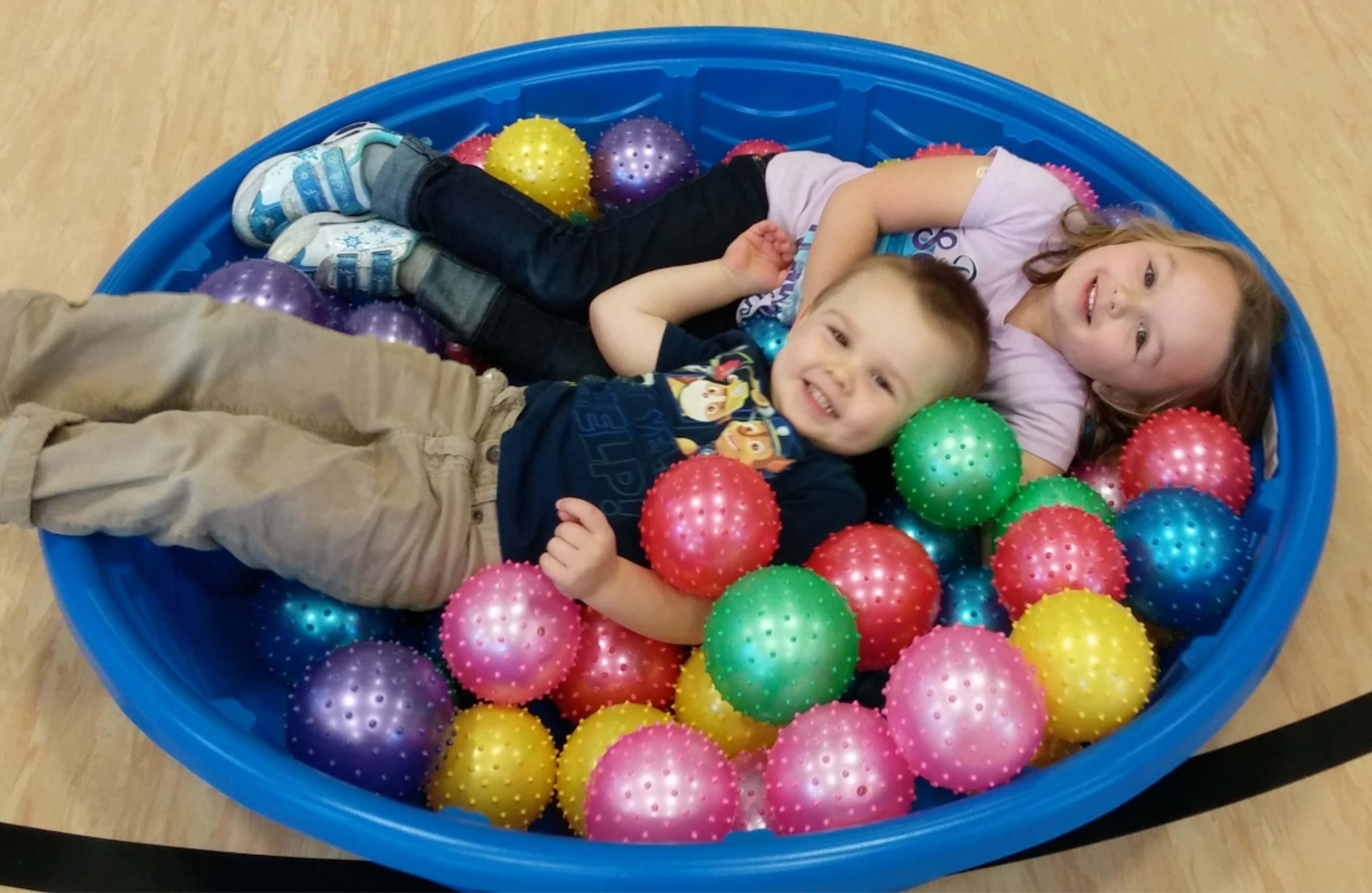 Two Kids Playing in a Pool Full of Plastic Toy Balls