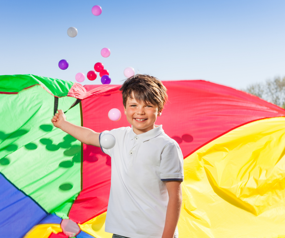 Child playing with parachute and balls