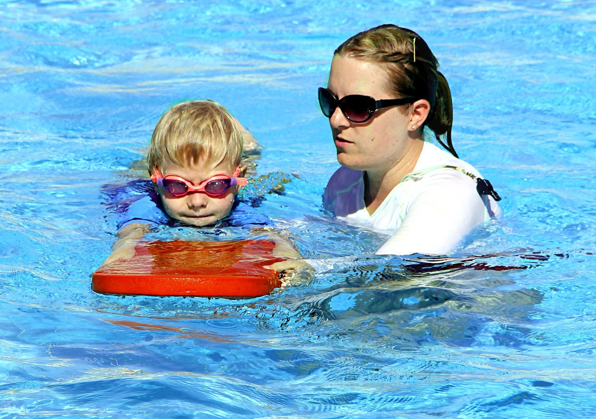 child and lifeguard during a swimming lesson