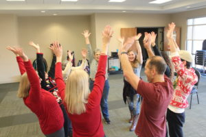 Group Partcipating in Laughter Yoga with Their Hands in the Air